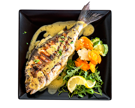 Top view of baked fish with vegeatables on a plate, isolated