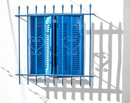 Blue window wooden shutters on white wall, Greece