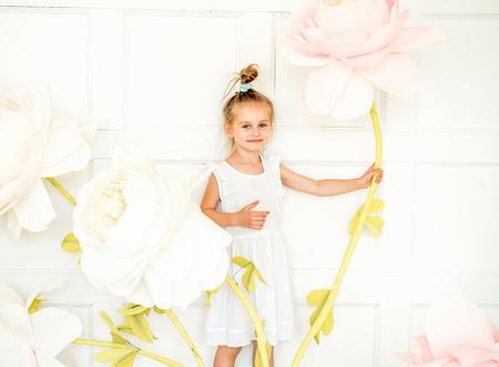 little girl posing in studio opposite decoration with artificial flowers Foto de archivo - 105805195