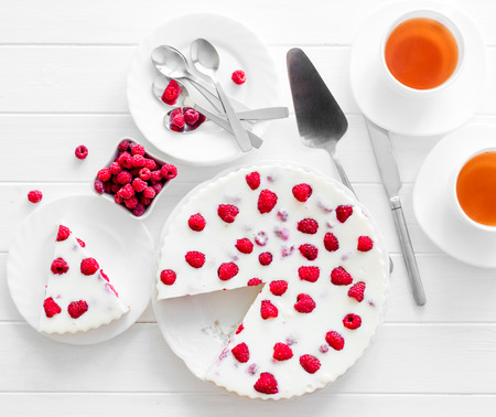Panna cotta raspberries on a wooden white serving table. top view
