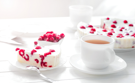Panna cotta raspberries on a wooden white serving table.