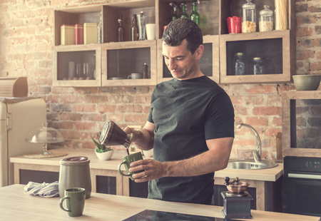 handsome man pours freshly brewed coffee into cups