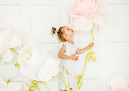 little girl posing in studio opposite decoration with artificial flowers