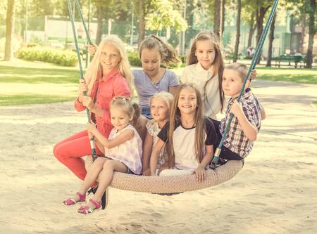Smiling kids sitting on the big swing