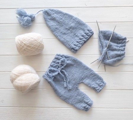 Blue knitted baby clothes with white knitting yarns