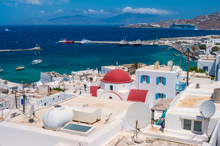 Typical whitewashed houses of Mykonos island with mountains on the background