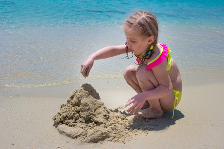 Child girl palying with the sand on the beach