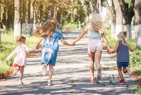 Little smiling girls running on the sunshine autumn alley by holding hands