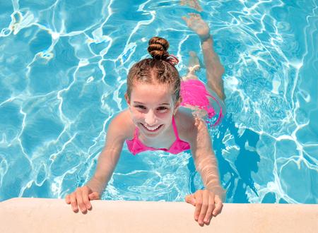 Jovencita en la piscina entrecerrando los ojos