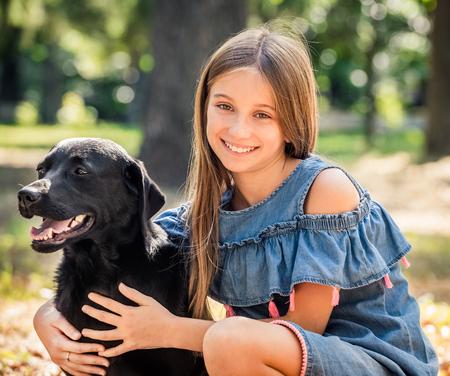 Teenage girl sit hugging a black dog in park 版權商用圖片