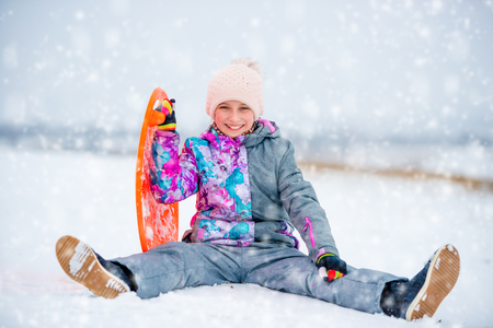 Girl with saucer sled on the snow Banque d'images - 107651584