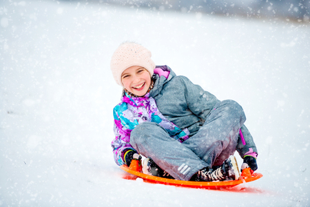 Girl sliding down the hill on saucer sled Banque d'images - 107651587