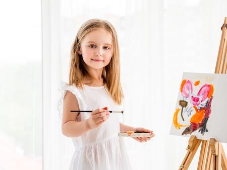 Portret van een klein meisje dat een afbeelding op ezel trekt