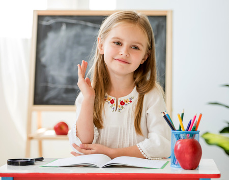 Little blond girl raise a hand for the answer sitting at the desk in the school classroom