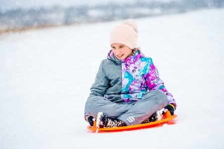 Girl sliding down the hill on saucer sled Banque d'images - 109880295