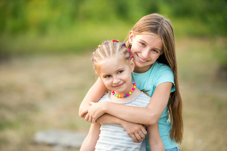 Little sisters hugging Stock Photo