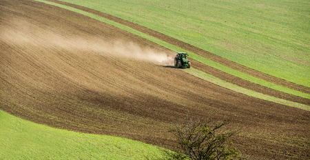 Aerial view of tractor pulling field on the slope of Moravia Stock Photo - 112764623