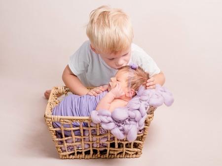 Little blond boy kissing little baby Stock fotó