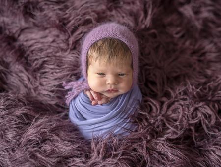 Little cute baby sitting on the dark pink blanket