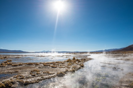 Sunshine view of surface covered with steam and geysers on the background of mountains in Bolivia