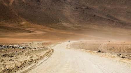 Top view of car riding on wide road of Bolivian sunshine desert covered with dust