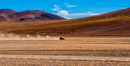 Black car riding on the road of Bolivian sunshine landscape