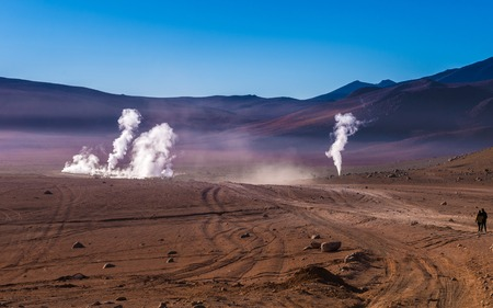 View of wide sunshine mountanious Bolivian desert and couple looking at the steaming geysers