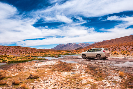 View of a car on the background of breathtaking landscape of Bolivia Stock Photo