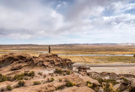 Hombre de pie en el borde de la colina rocosa en Bolivia Foto de archivo