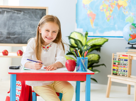 Little blond girl sit at the white desk and laughing in the school classroom