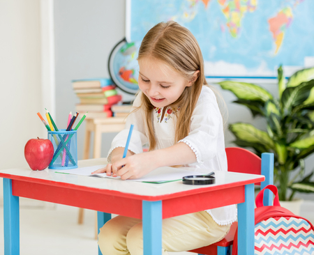 Little blond girl writing classwork in the school classroom