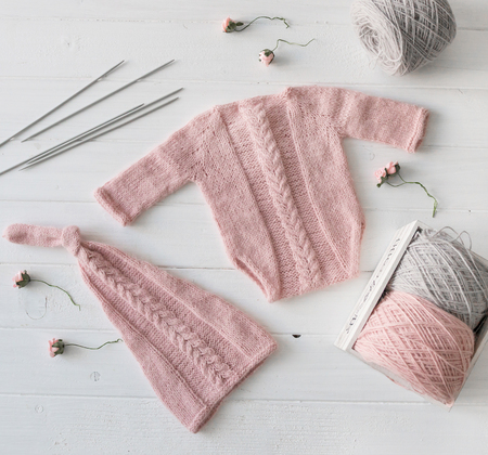 Knitted handmade clothes for infant girls, top view Stockfoto