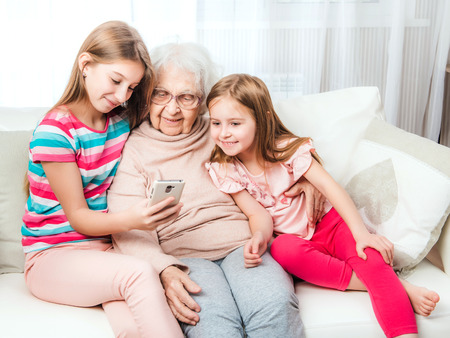 Smiling granddaughters with great-grandmother