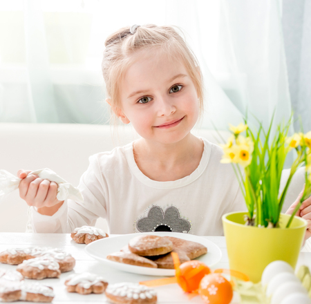 Little girl coveing gingerbread with icing