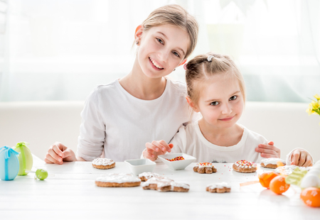 Two sisters decorating gingerbread cookies on kitchen