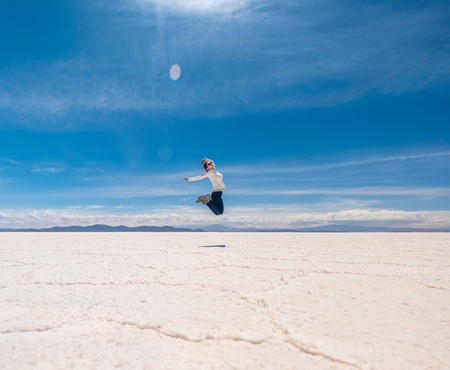 Girl in a jump in sunshine Salar de Uyuni