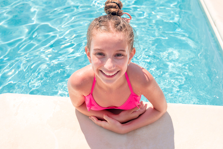 Teen girl in swimming pool squinting her eyes Imagens