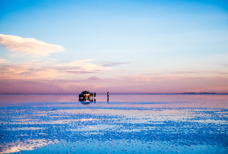 Amazing scenery of the spacious Salar de Uyuni with cars on it
