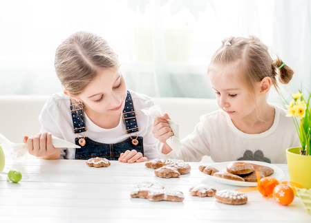 Child girl decorating Easter cookies