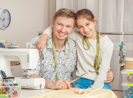 little girl and her dad in a sewing workshop Stockfoto
