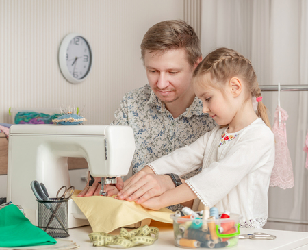 little girl and her dad in a sewing workshop Stock Photo