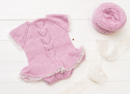 Composition of white-pink knitted suit and hat Stock Photo