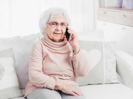 Prababcia rozmawia przez smartfon Zdjęcie Seryjne