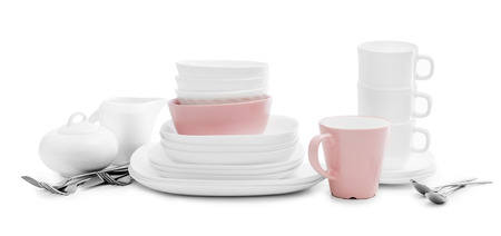 White and pink plates, sugar bowl and mugs on light background