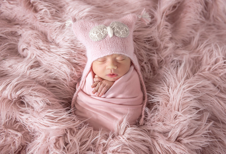 Newborn in beanie hat on a shaggy carpet