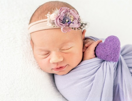 Infant newborn in flowery band and blanket, secured with a braid 版權商用圖片