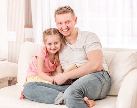 Dad and daughter sitting on the couch Stock Photo