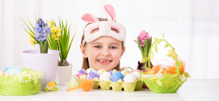 The child peals from behind the Easter decorations Stock Photo