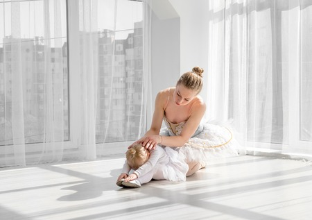 Female ballet dancer teaching little girl doing exarcises for stretching Stock Photo