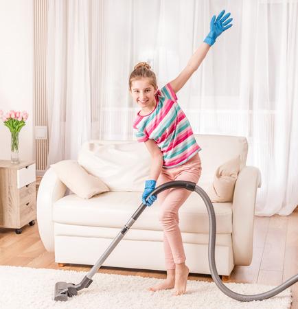 GIrl is using vacuum cleaner Imagens - 121237531